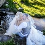 bride and groom by the creek